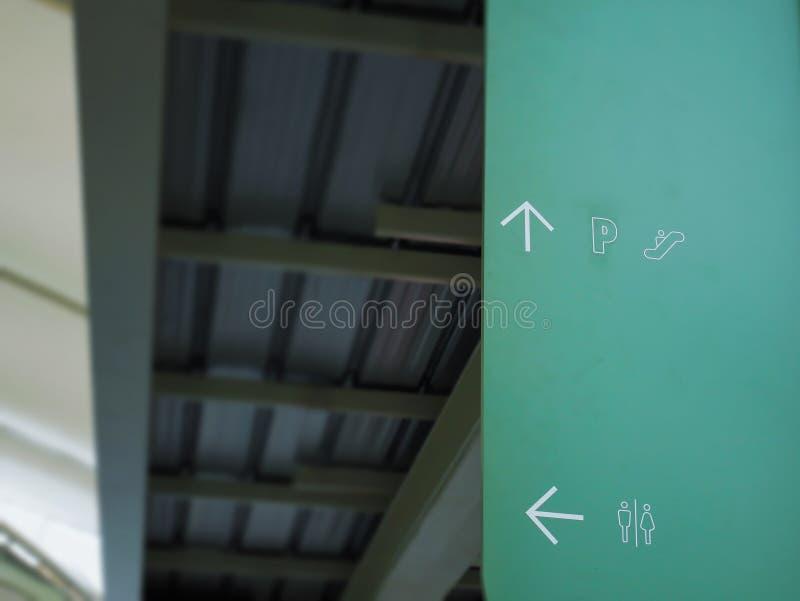 Riktningstecken och symboler av parkeringsplatsen, rulltrappan och toaletten arkivbilder
