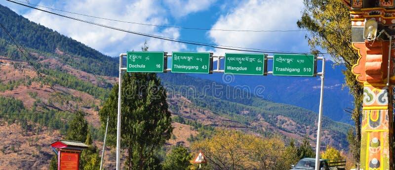 Riktningsvägmärken på huvudvägen till Dochala i Bhutan arkivbild