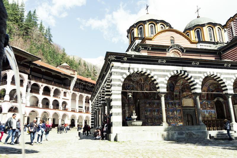 Rila/Bulgarien - 04142019: Rila kloster med insn?at den ortodoxa kyrkan f?r berg arkivfoto
