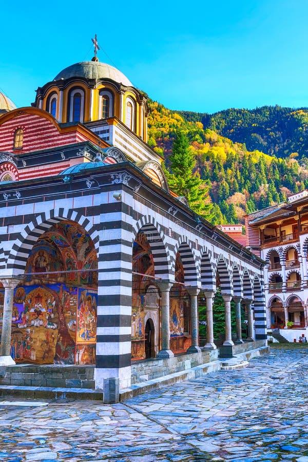 Rila Monastery, Bulgaria and autumn mountains. Bulgaria, Rila monastery view with autumn mountain trees at background stock image
