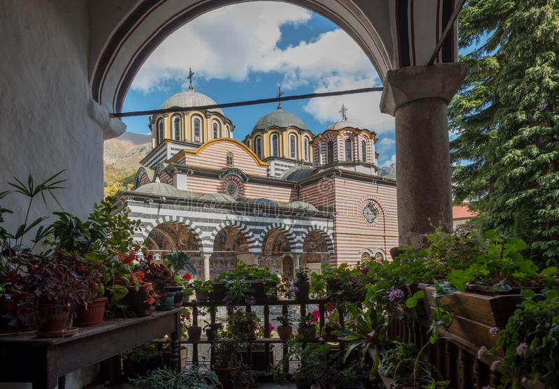 Rila Monastery`s main church framed by arch, plants and flowers stock photography