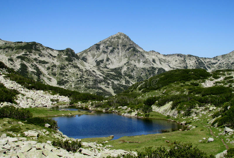 Rila mountains in Bulgaria, deep blue lakes and gray rock summit during the sunny day with clear blue sky. Rila mountains in Bulgaria, deep blue lakes and gray royalty free stock image