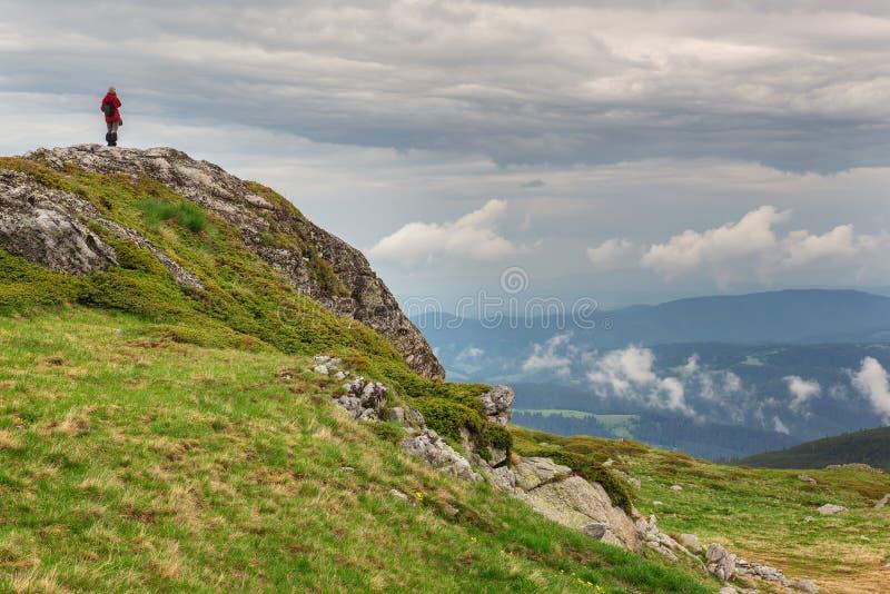 Rila mountains. A woman on the top of a rock enjoys the spring view of Rila mountains, Bulgaria stock image