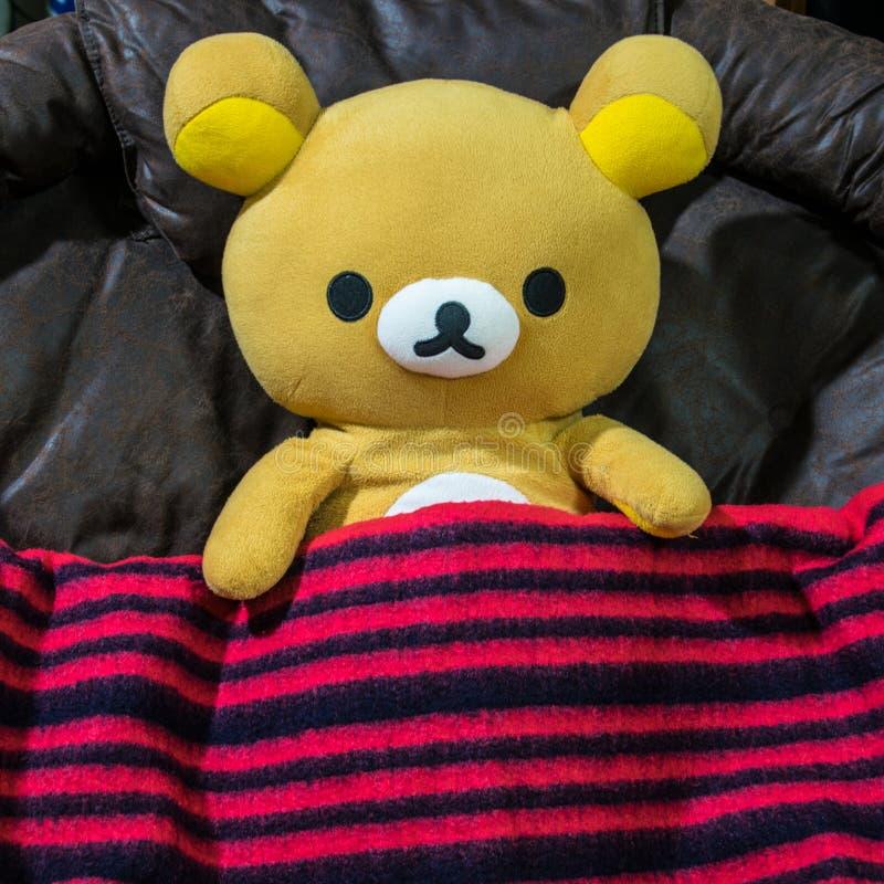 Rilakkuma-Puppe bedeckt durch die rote Decke mit Schwarzem gestreift lizenzfreie stockfotos