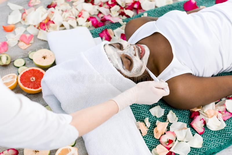Rilassamento di riposo della bella ragazza africana nella località di soggiorno di stazione termale con gli occhi chiusi mentre i immagine stock