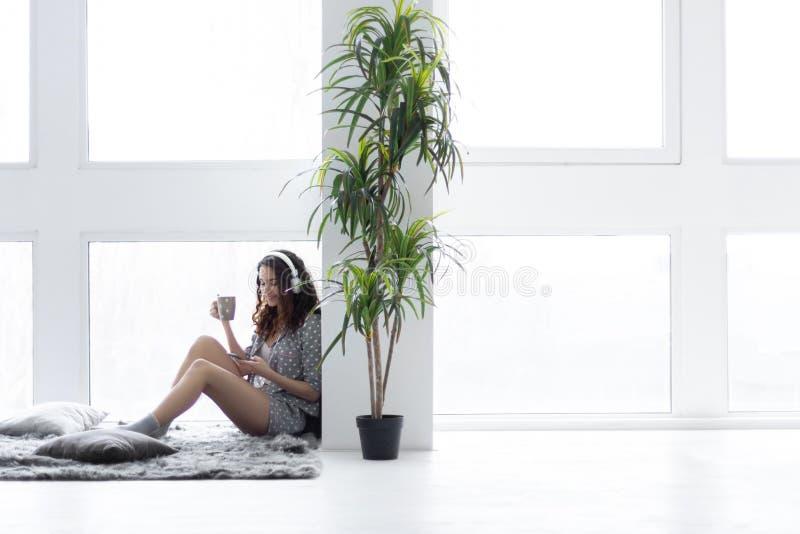 Rilassamento femminile ed ascoltare la musica a casa fotografia stock libera da diritti