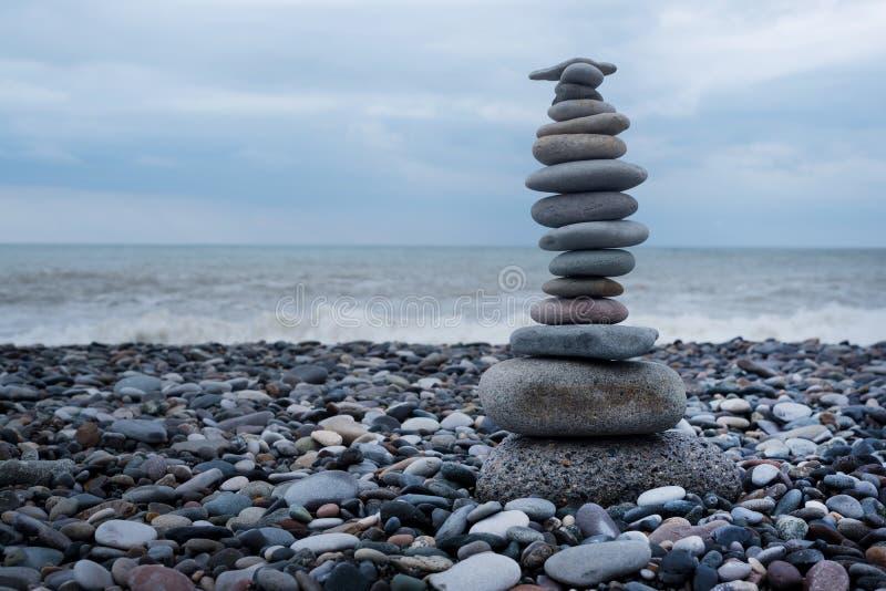 Rilassamento in mare Pila di pietre sul fondo della natura della spiaggia Cairn di pietra su fondo confuso verde immagine stock