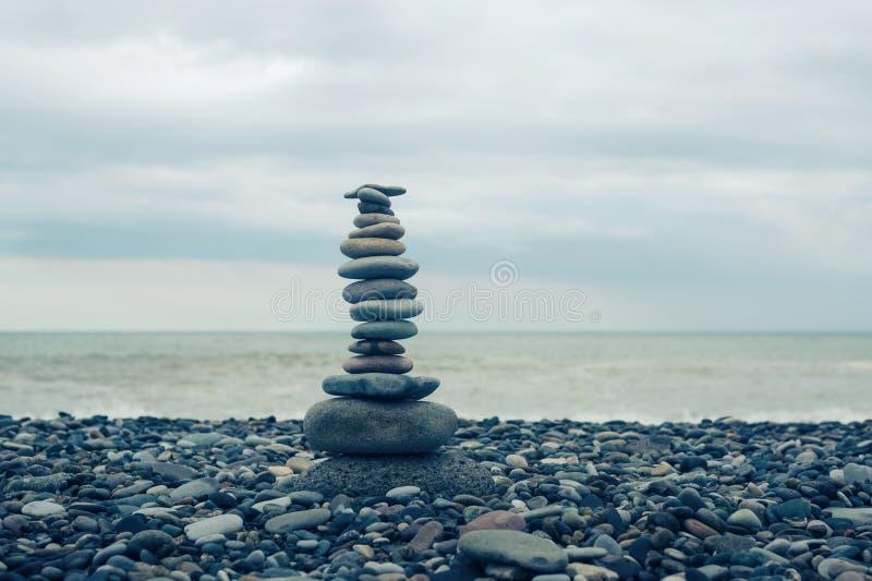 Rilassamento in mare Pila di pietre sulla spiaggia - fondo della natura Cairn di pietra su fondo confuso, sui ciottoli e sulle pi fotografia stock