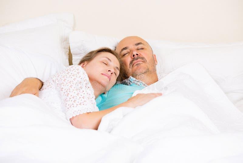Rilassamento maturo felice delle coppie, addormentato in un letto immagine stock libera da diritti