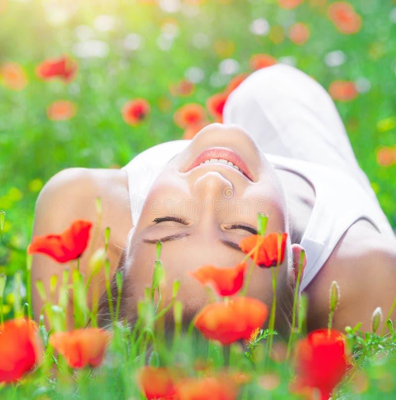 Rilassamento sul giacimento di fiore del papavero fotografie stock