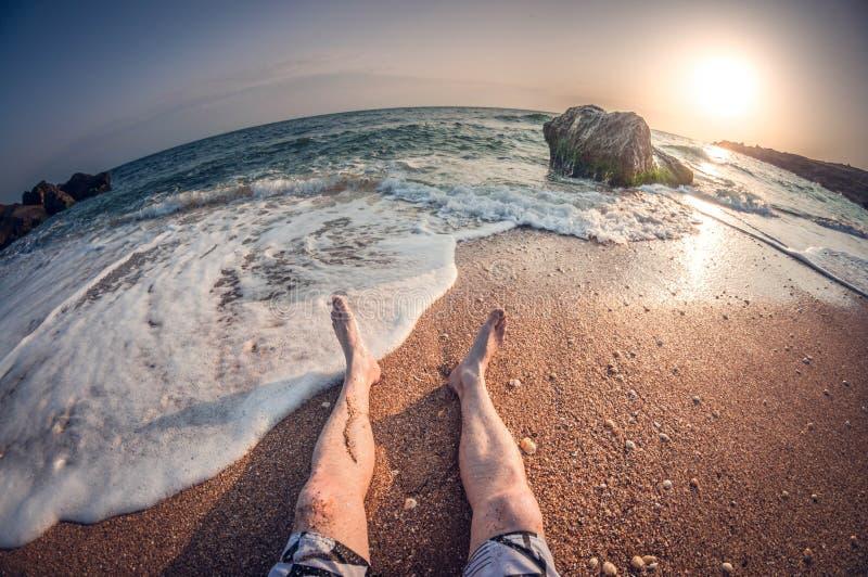 Rilassamento sul mare che si siede sulla spiaggia, sul tramonto, vista in prima persona, distorsione del fisheye fotografia stock libera da diritti