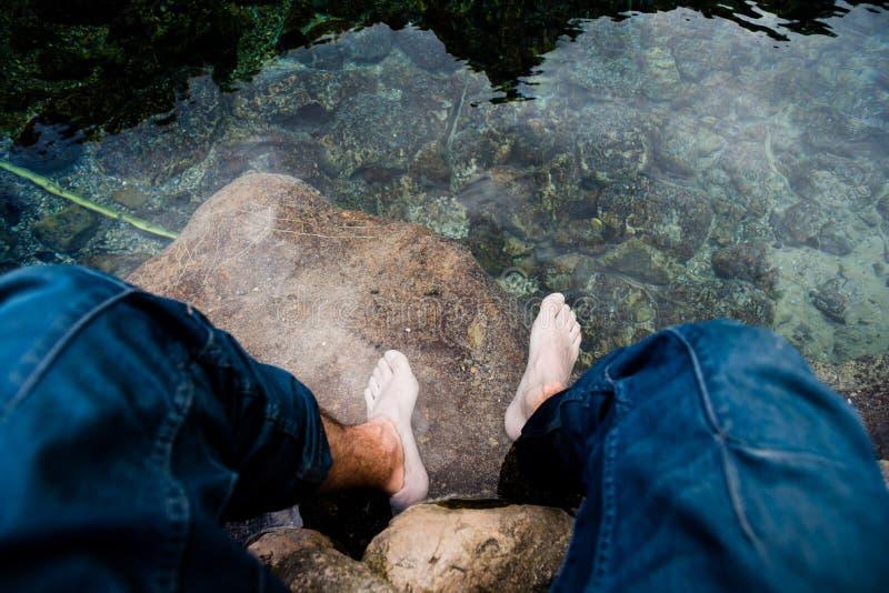 Rilassandosi inzuppando i piedi in chiara acqua fotografia stock