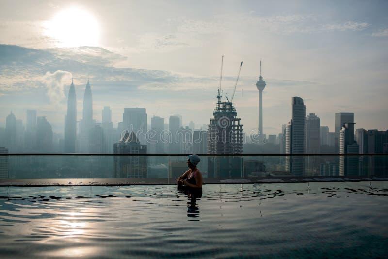 Rilassandosi nello stagno e godere del panorama della città Kuala Lumpur, Malesia immagini stock