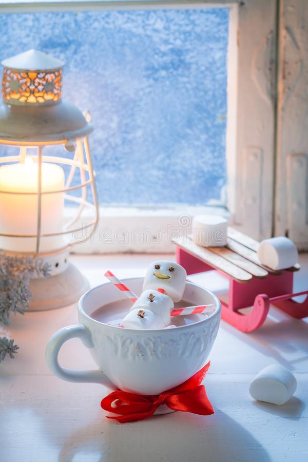 Rilassandosi in pupazzo di neve caldo del cacao per il Natale dalla finestra congelata fotografia stock