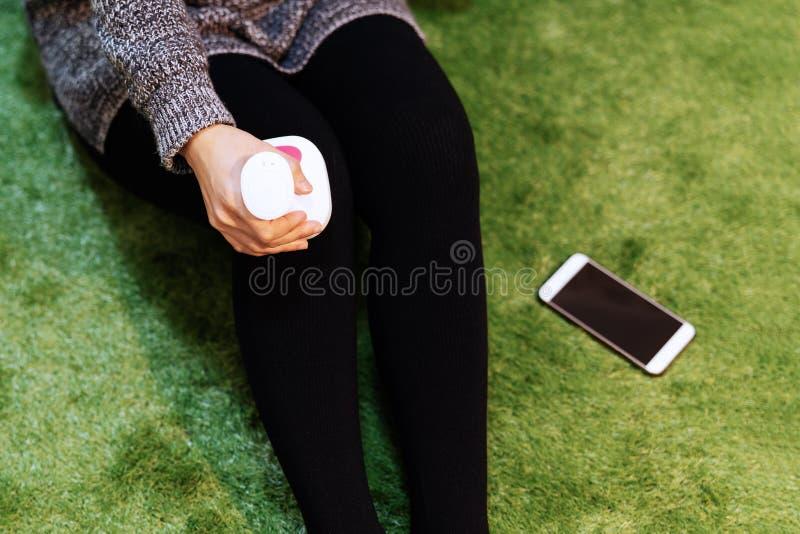 Rilassi e massaggi, ginocchio e macchina elettrici di massaggio della gamba sul concetto delle donne gamba, del primo piano, di s fotografia stock libera da diritti