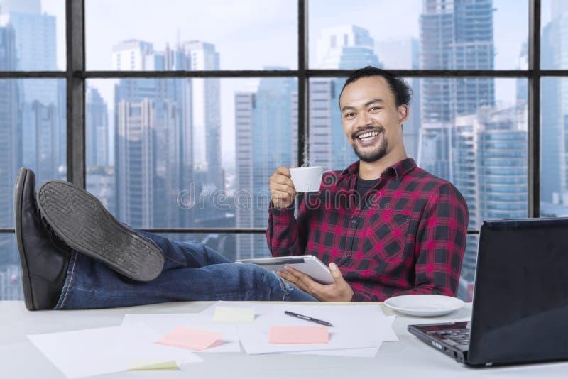 Rilassi il lavoratore professionista con una tazza di caffè ed i piedi sulla tavola di funzionamento fotografia stock