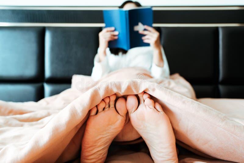 Rilassi il piede della donna che si siede sul letto che legge il libro fotografia stock libera da diritti