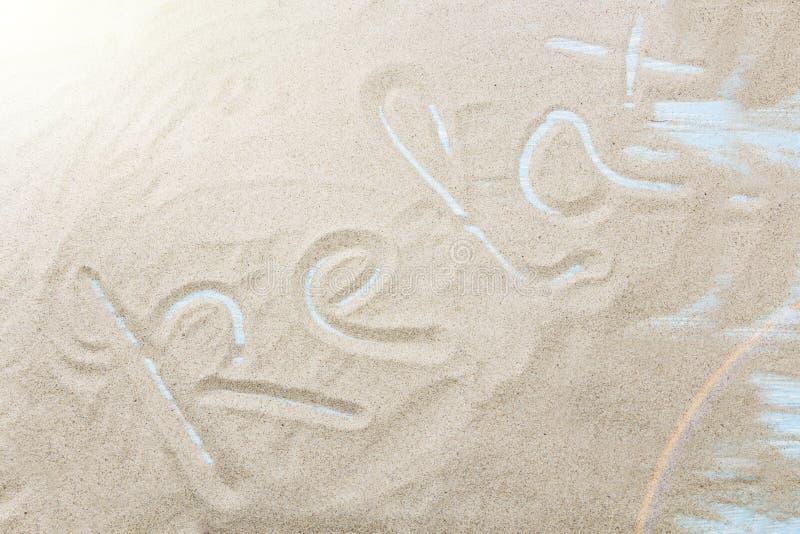 Rilassi scritto a mano in sabbia su una spiaggia immagini stock
