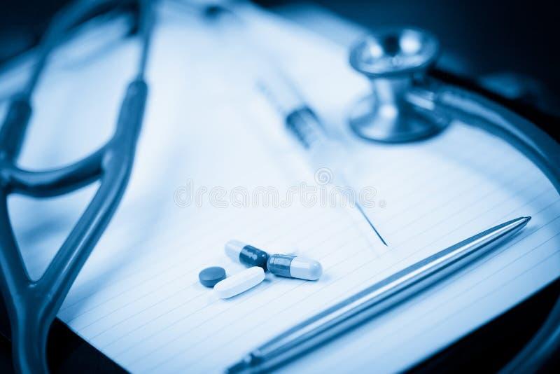 Rilievo di nota con lo stetoscopio e la penna avanti fotografia stock libera da diritti
