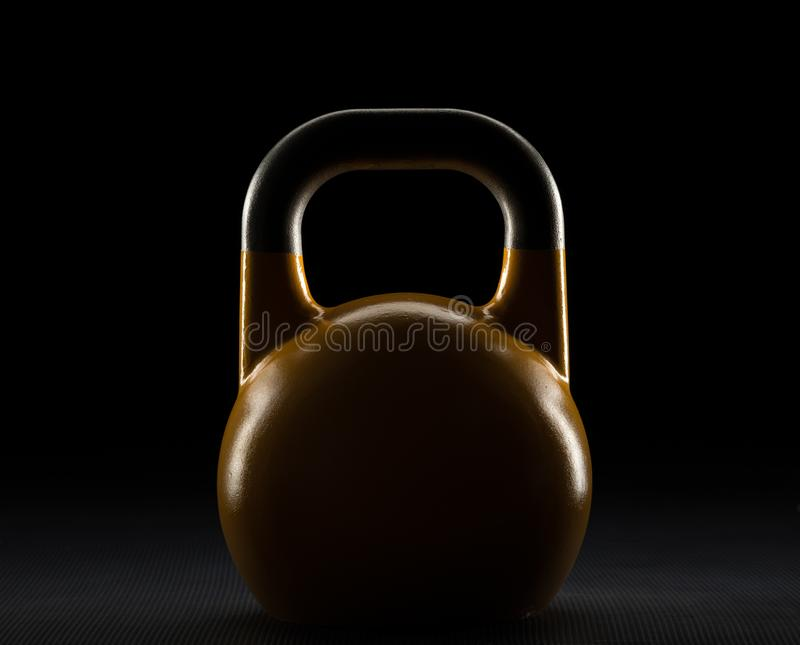 Rim lit yellow competition kettlebell silhouette on a weight training gym floor stock photo