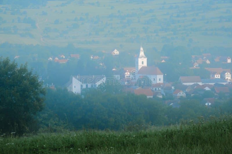 Rimetea wioska w Transylvania, Rumunia podczas mgłowego wschód słońca, jak widzieć od podwyższonej lokacji na niedalekim wzgórzu fotografia royalty free