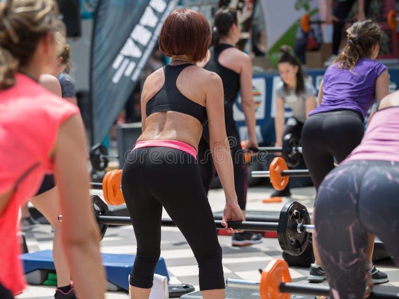 Rimini, Italië - mei 2019: Meisjes die Weighthijsoefeningen doen in de openlucht Gym met Step Platform: Geschiktheid royalty-vrije stock foto