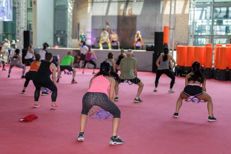 Rimini, Italië - mei 2019:Meisjes oefenen met Gym double handle Dumbbell in Fitness Class bij Gym met muziek en leraar op Stage stock fotografie