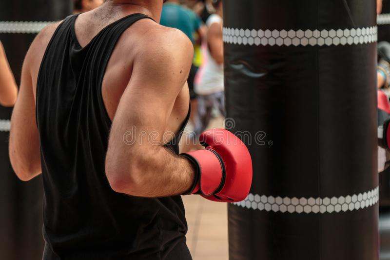 Rimini, Italia - può 2016: Allenamento di pugilato e di forma fisica: Ragazzo con i guanti rossi ed il punching ball nero immagini stock