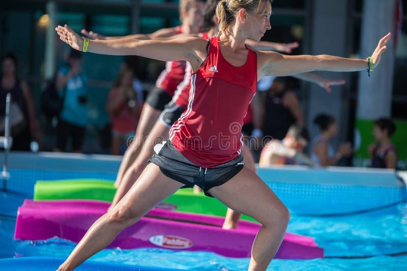 Rimini, Italie - juin 2017 : Filles faisant des exercices sur le tapis de flottement de forme physique dans une piscine extérieur photos libres de droits