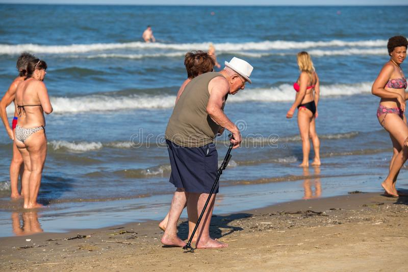 Old man with a cane walking along the beach royalty free stock photos