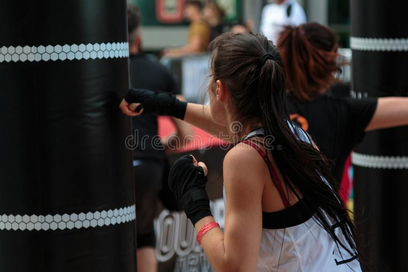 Rimini, Italy - may 2016:Young Girl with Shorts and White Tank Top: Fitness Boxing Workout with Punching Bag stock image