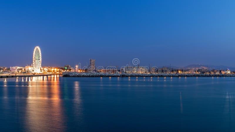 Rimini waterfront cityscape at evening. Urban night lights. Seaport stock image