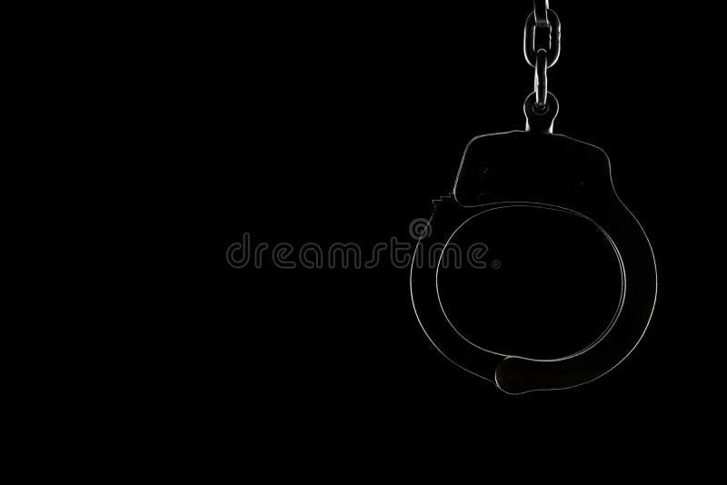 Rimlit låste handbojor på en svart bakgrund med kopieringsutrymme royaltyfri fotografi