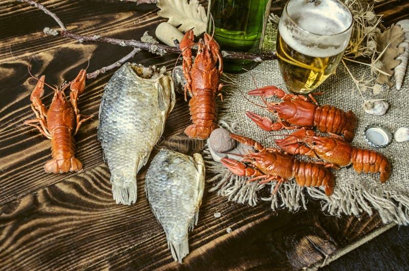 Rimmad kokt röd kräfta med den torkade rimmade fisken, exponeringsglas med öl och en flaska av öl arkivbild