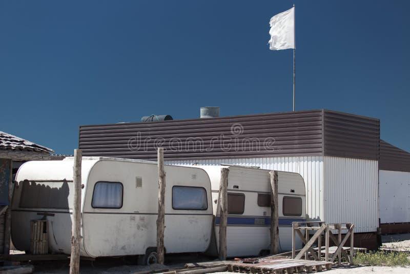Rimorchi di campeggio accanto alla spuma-stazione sulla spiaggia soleggiata immagine stock