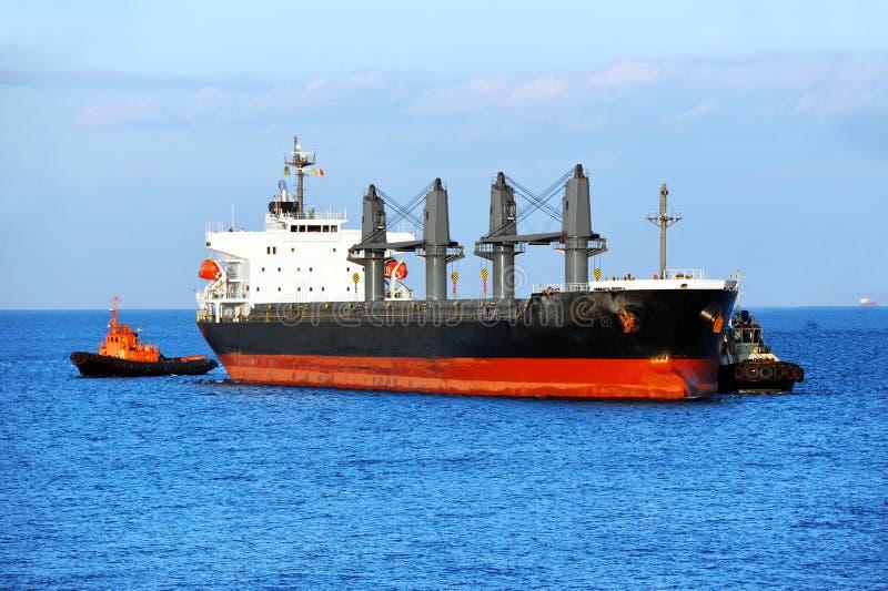 Rimorchiatore che assiste la nave da carico in serie fotografia stock libera da diritti