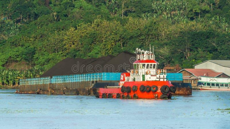 Rimorchiatore che tira chiatta in pieno di carbone nero nel fiume di Mahakam, Borneo, Indonesia fotografia stock libera da diritti