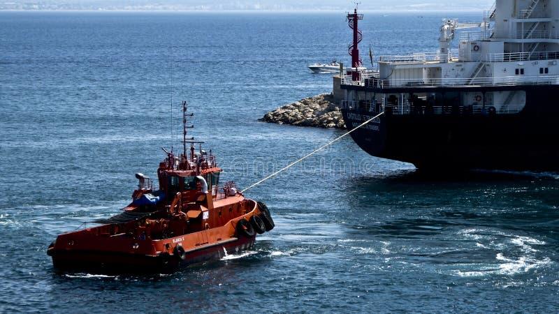 Rimorchiatore rosso che tira una nave immagine stock libera da diritti