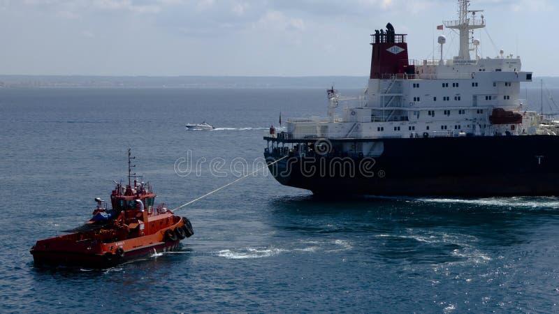 Rimorchiatore rosso che tira una nave fotografie stock libere da diritti