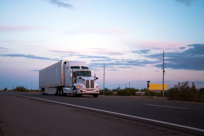 Rimorchio del camion dei semi che va sulla strada dell'Arizona nel tramonto fotografie stock libere da diritti