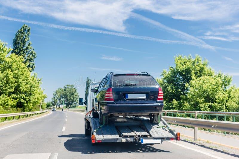 Rimorchio del trasportatore di automobile con l'automobile Automobile trasportata sul camion di rimorchio dell'evacuazione sulla  fotografie stock libere da diritti