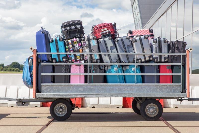 Rimorchio sull'aeroporto riempito di valigie immagini stock libere da diritti