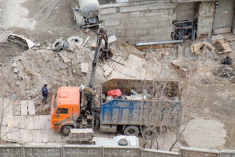 Rimozione dei detriti del cantiere Camion con caricamento della gru per la ferraglia fotografia stock
