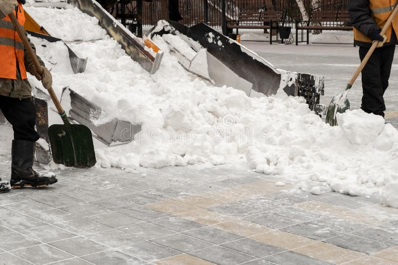 Rimozione di neve sulle vie Primo piano di uno spazzaneve e dei lavoratori della strada con le pale La gente ed automobili Abbond fotografia stock