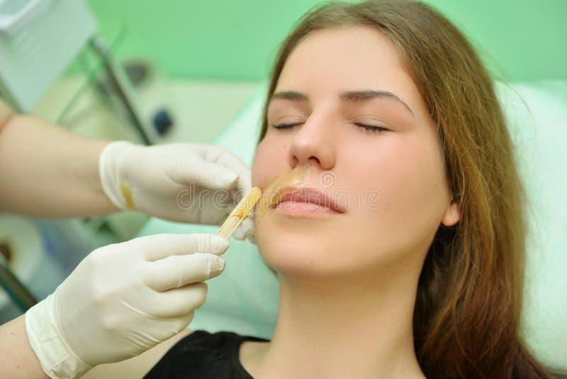Rimuovendo i baffi di una donna con la cera calda in un salone di bellezza fotografia stock libera da diritti