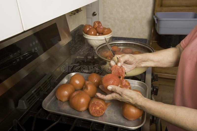 Rimuovendo pelle dai pomodori. fotografia stock
