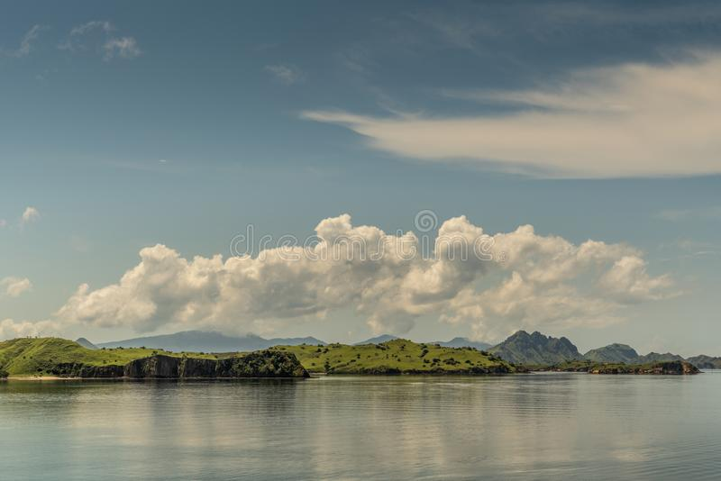 Flat islets off Rinca Island westside coast, Indonesia. Rinca Island, Indonesia - February 24, 2019: Flat islets off Westside coast in Savu Sea under cloudscape stock images