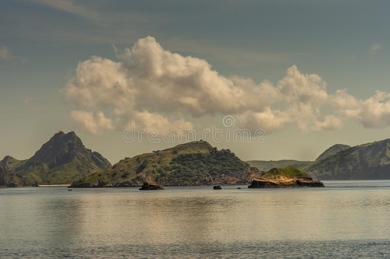 Islets and beaches on Rinca Island westside coast, Indonesia. Rinca Island, Indonesia - February 24, 2019: Islets and Beaches surrounded by green hills on royalty free stock photo