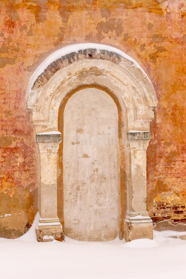 Rinchiuso bricked sulla porta con un portico e su due colonne dai lati sui precedenti di vecchia parete intonacata arancio dentro fotografie stock libere da diritti