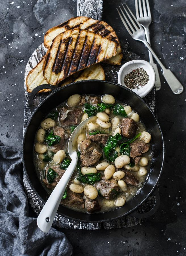Rindfleisch, Bohnen, langsames Kochereintopfgericht des Spinats in einer Wanne auf einem hölzernen Brett auf einem dunklen Hinter lizenzfreies stockbild